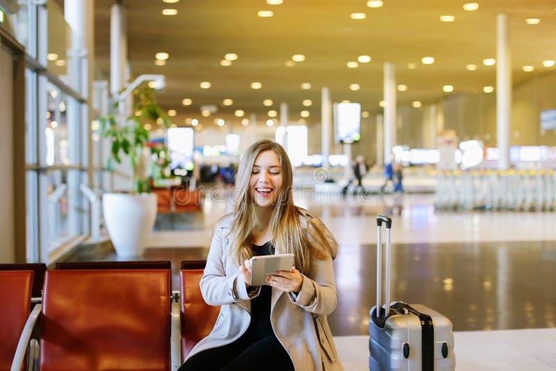 Η νέα συνεδρίαση γυναικών στην αίθουσα αερολιμένων με την ταμπλέτα και, χρησιμοποιώντας Διαδίκτυο στοκ εικόνες