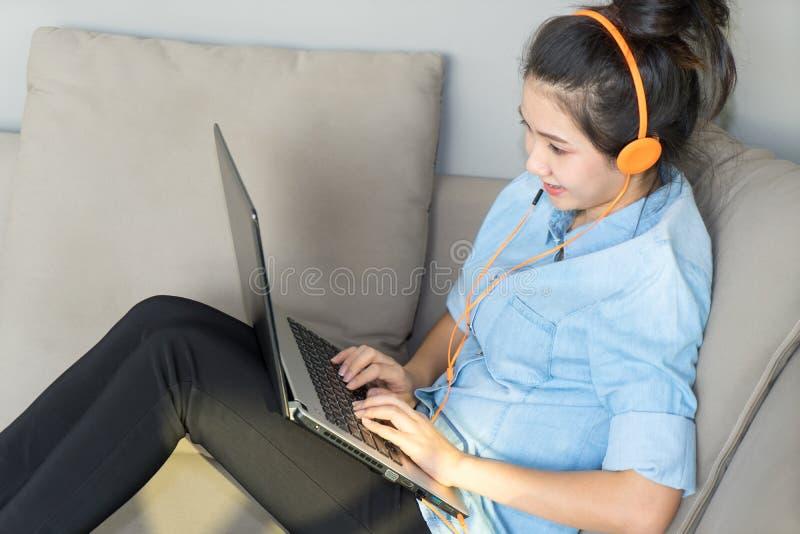 Η νέα συνεδρίαση γυναικών στον καναπέ με το lap-top και τα ακουστικά απολαμβάνουν το αγαπημένο τραγούδι στοκ εικόνα με δικαίωμα ελεύθερης χρήσης
