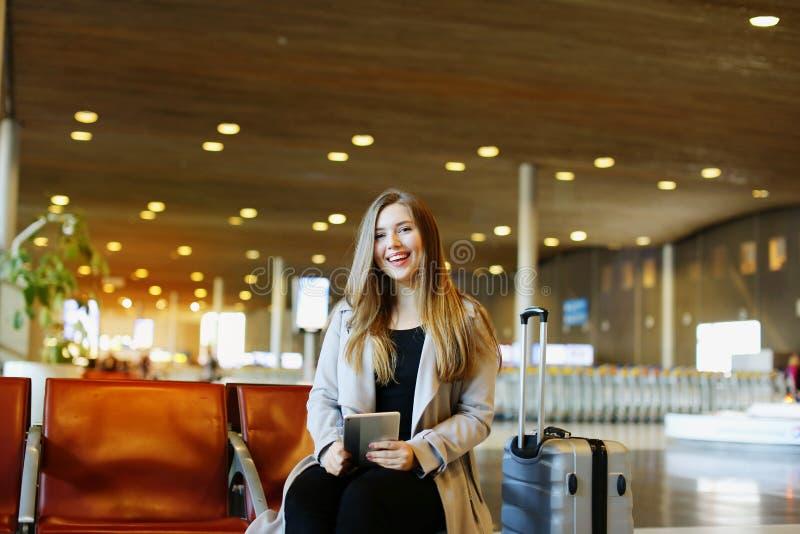 Η νέα συνεδρίαση γυναικών χαμόγελου στην αίθουσα αερολιμένων με την ταμπλέτα και στοκ φωτογραφία
