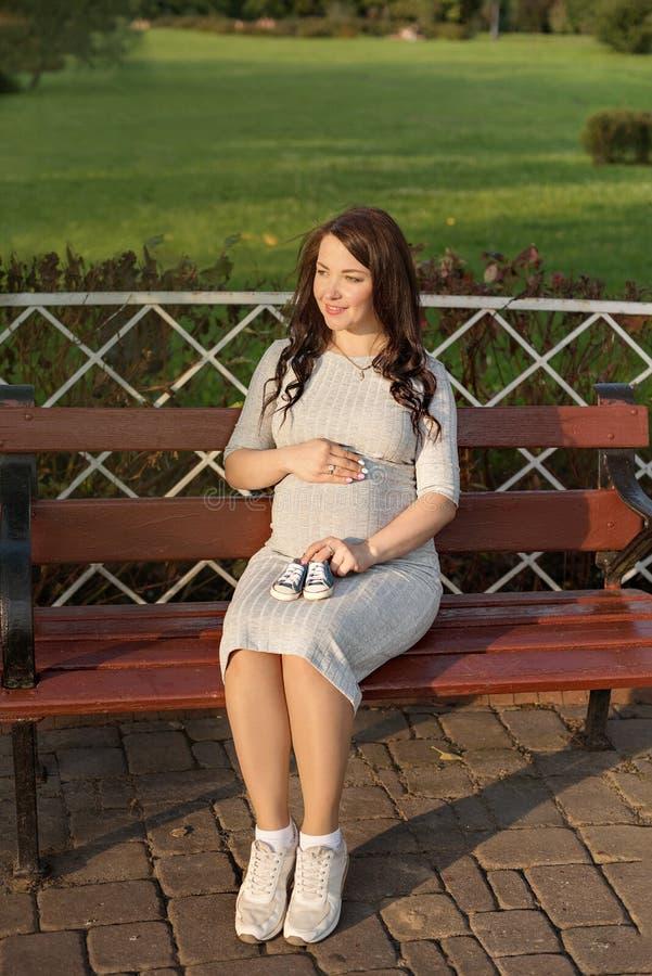 Η νέα συνεδρίαση εγκύων γυναικών στον πάγκο στο πάρκο και κρατά τα πάνινα παπούτσια για νεογέννητο στοκ εικόνες