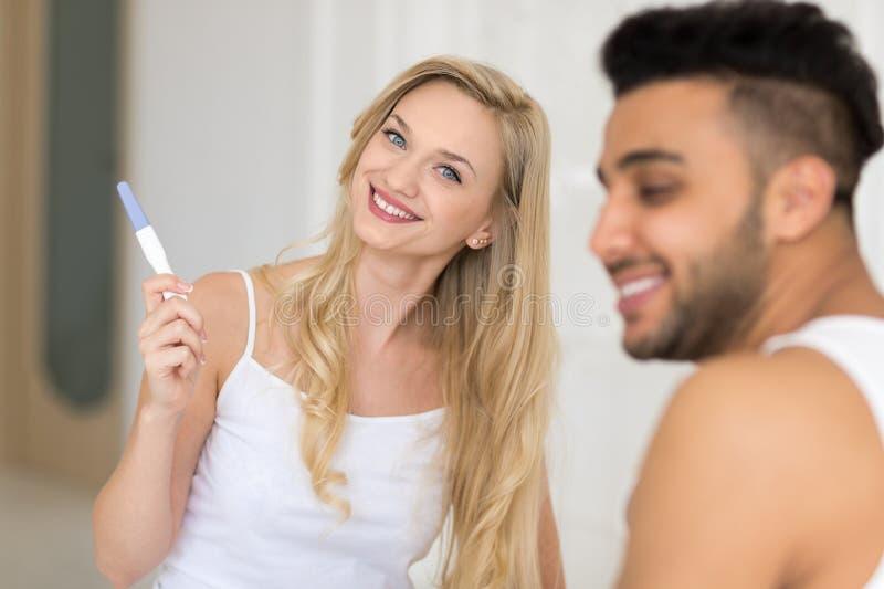 Η νέα συνεδρίαση ζεύγους στο κρεβάτι, ευτυχής γυναίκα χαμόγελου παρουσιάζει στο συγκινημένο έκπληκτο άνδρα θετική δοκιμή εγκυμοσύ στοκ φωτογραφίες