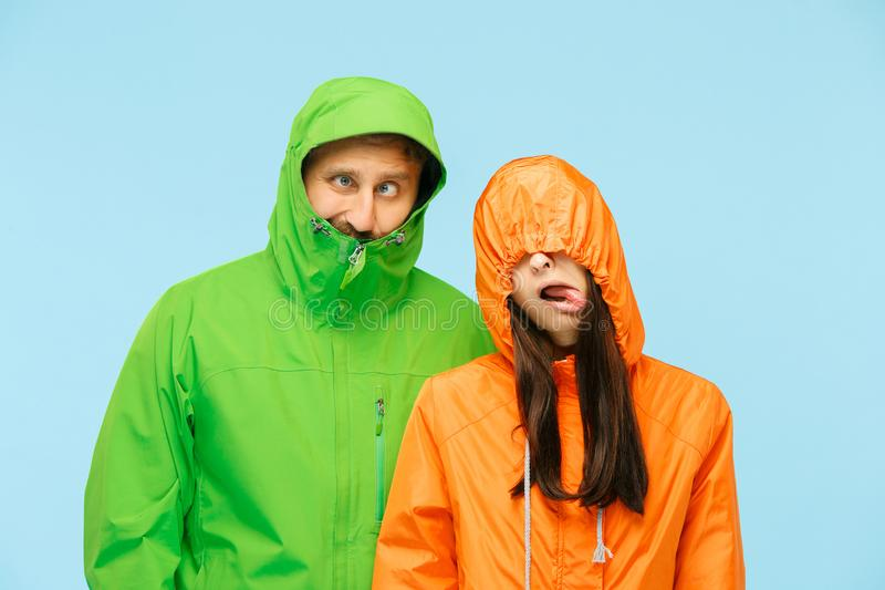 Η νέα τοποθέτηση couplel στο στούντιο στα σακάκια φθινοπώρου που απομονώνονται στο μπλε στοκ εικόνες