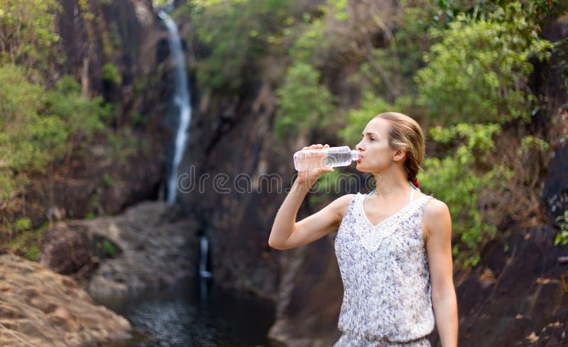 Η νέα υγιής γυναίκα πίνει το νερό από το μπουκάλι. Υπαίθριος στοκ φωτογραφίες