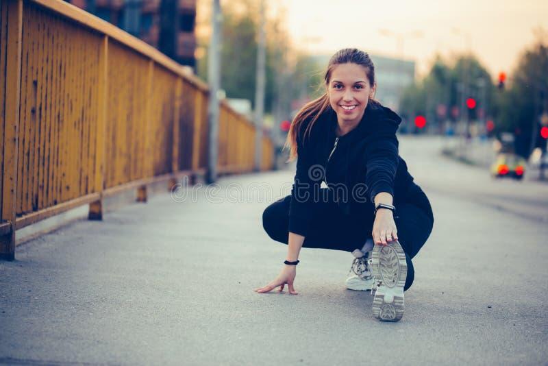 Η νέα φίλαθλη γυναίκα κάνει την τεντώνοντας άσκηση στη γέφυρα ποταμών στοκ φωτογραφίες με δικαίωμα ελεύθερης χρήσης