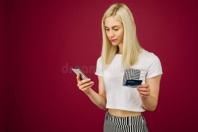 Η νέα χαμογελώντας γυναίκα αγοράζει on-line Κρατά ένα smartphone και μια πιστωτική κάρτα διαθέσιμα στοκ φωτογραφία