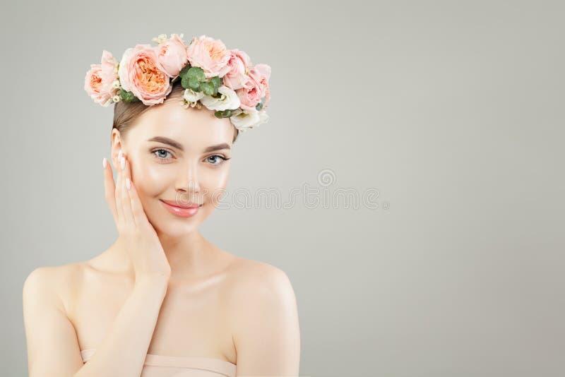 Η νέα χαμογελώντας γυναίκα με το υγιές δέρμα και τα ρόδινα τριαντάφυλλα ανθίζει στο γκρίζο υπόβαθρο στοκ εικόνες με δικαίωμα ελεύθερης χρήσης