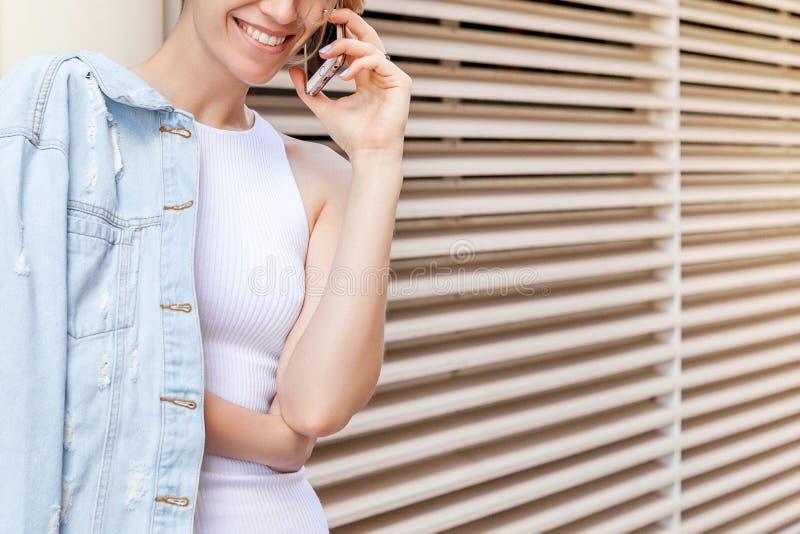 Η νέα χαμογελώντας γυναίκα μιλά τηλεφωνικώς στοκ εικόνες