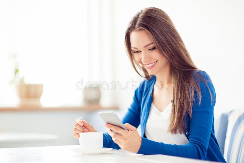 Η νέα χαριτωμένη κυρία κοιτάζει βιαστικά στο pda της ενώ έχοντας τον καφέ στον καφέ Είναι στην περιστασιακή εξάρτηση, χαμόγελο, π στοκ εικόνες