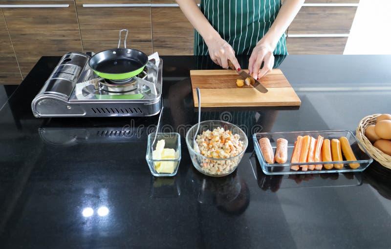 Η νέα όμορφη ασιατική γυναίκα τεμαχίζει το λουκάνικο στο ξύλινο πιάτο στο μαύρο μαρμάρινο πίνακα επίσης με τα αυγά, το βουτύρου,  στοκ φωτογραφίες με δικαίωμα ελεύθερης χρήσης