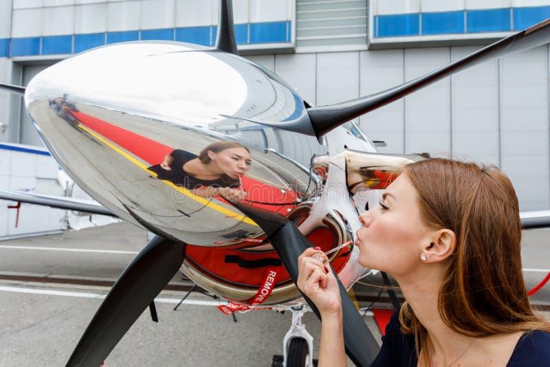 Η νέα όμορφη γυναίκα αποτελεί το πρόσωπο κοιτάζοντας στην αντανάκλαση fairing χρωμίου ενός προωστήρα του επιχειρησιακού αεριωθούμ στοκ φωτογραφία με δικαίωμα ελεύθερης χρήσης