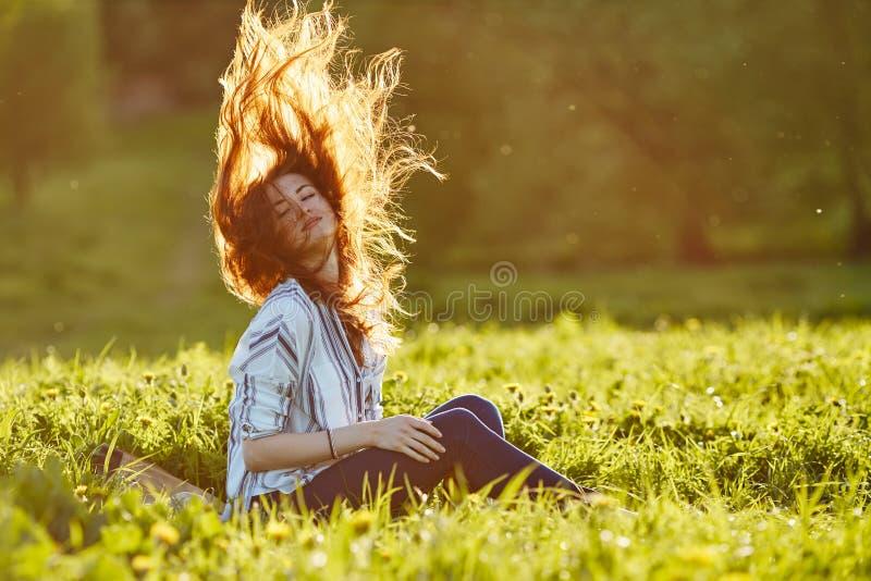 Η νέα όμορφη γυναίκα κάθεται σε ένα λιβάδι και ρίχνει επάνω στην τρίχα της στοκ εικόνες με δικαίωμα ελεύθερης χρήσης