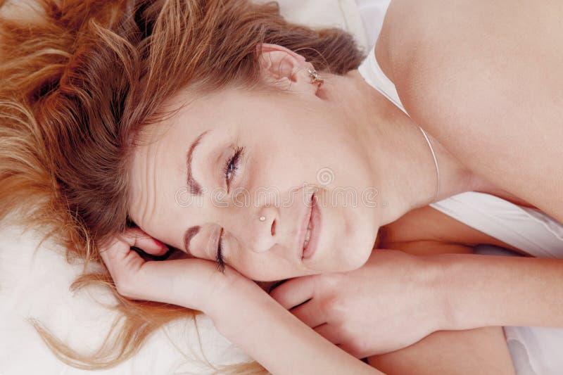 Η νέα όμορφη γυναίκα με τα μακριά ξανθά μαλλιά στο κρεβάτι φορά ` τ θέλει στοκ εικόνα