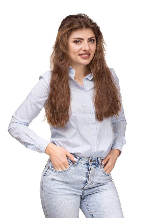Η νέα όμορφη γυναίκα με τη μακριά σγουρή τρίχα που χαμογελά, κράτημα παραδίδει τις τσέπες στοκ φωτογραφία