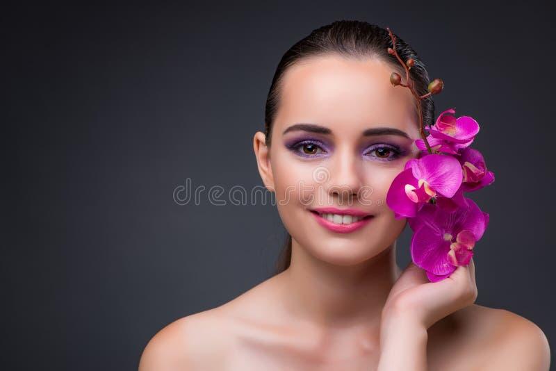 Η νέα όμορφη γυναίκα με το λουλούδι ορχιδεών στοκ φωτογραφίες με δικαίωμα ελεύθερης χρήσης