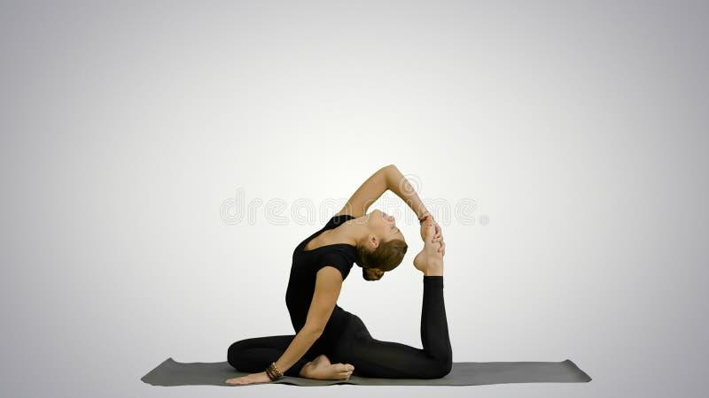 Η νέα όμορφη γυναίκα που κάνει τη γιόγκα θέτει, τεντώνοντας το σώμα της στο άσπρο υπόβαθρο στοκ εικόνα με δικαίωμα ελεύθερης χρήσης