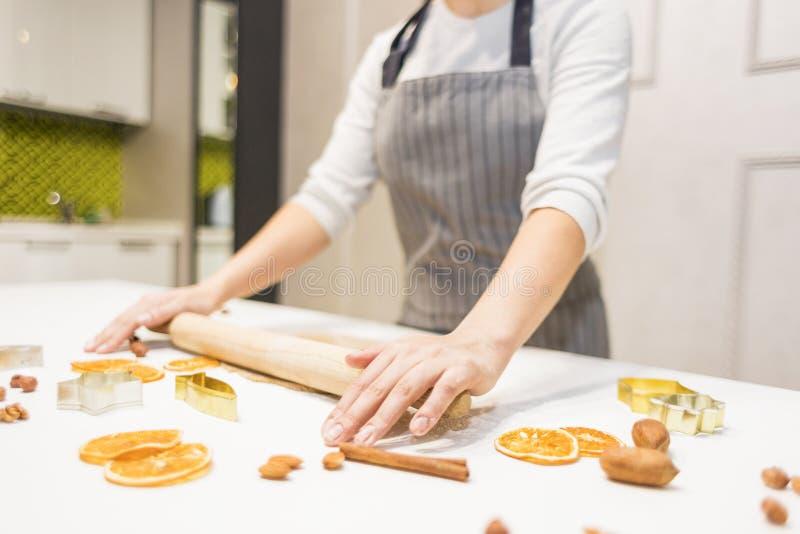 Η νέα όμορφη γυναίκα προετοιμάζει τη ζύμη και ψήνει το μελόψωμο και τα μπισκότα στην κουζίνα Χαρούμενα Χριστούγεννα και ευτυχής ν στοκ φωτογραφίες