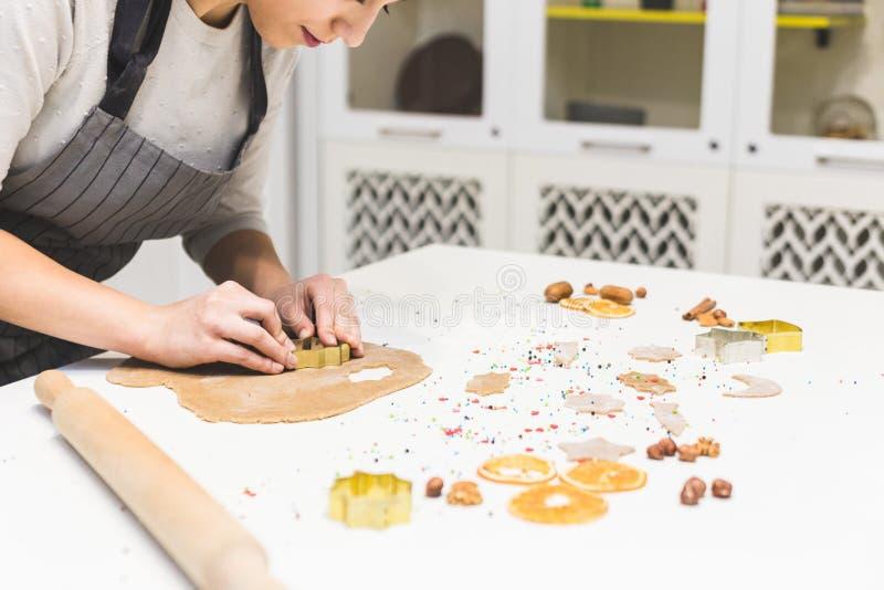 Η νέα όμορφη γυναίκα προετοιμάζει τη ζύμη και ψήνει το μελόψωμο και τα μπισκότα στην κουζίνα Κάνει μια μορφή αστεριών στοκ φωτογραφίες