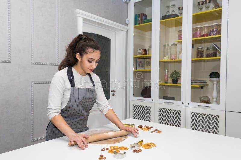Η νέα όμορφη γυναίκα προετοιμάζει τη ζύμη και ψήνει το μελόψωμο και τα μπισκότα στην κουζίνα Χαρούμενα Χριστούγεννα και ευτυχής ν στοκ φωτογραφία