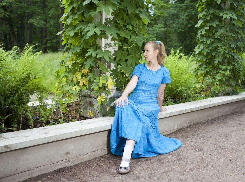 Η νέα όμορφη γυναίκα σε ένα μπλε φόρεμα στον άξονα τύλιξε πράσινο bindweed στοκ εικόνα