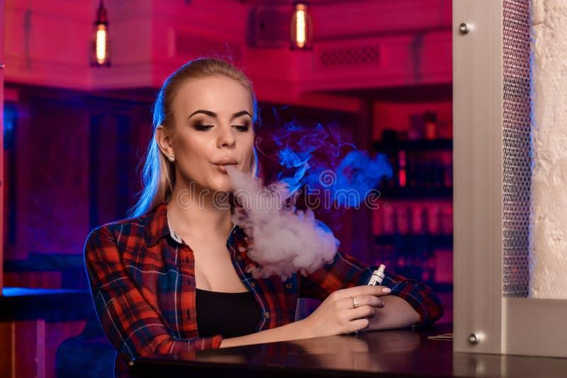 Η νέα όμορφη γυναίκα σε ένα πουκάμισο σε ένα κλουβί καπνίζει ένα ηλεκτρονικό τσιγάρο στο φραγμό vape στοκ φωτογραφίες με δικαίωμα ελεύθερης χρήσης