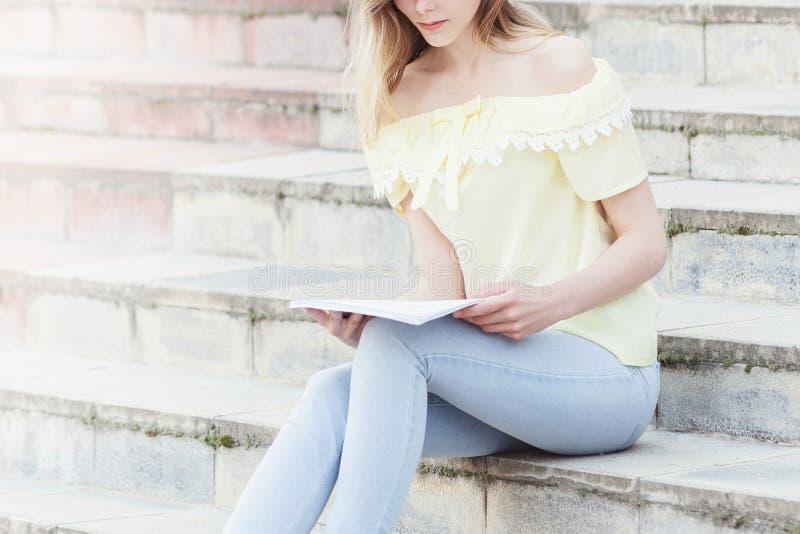Η νέα όμορφη γυναίκα σπουδαστής διαβάζει στα σκαλοπάτια στοκ φωτογραφία με δικαίωμα ελεύθερης χρήσης