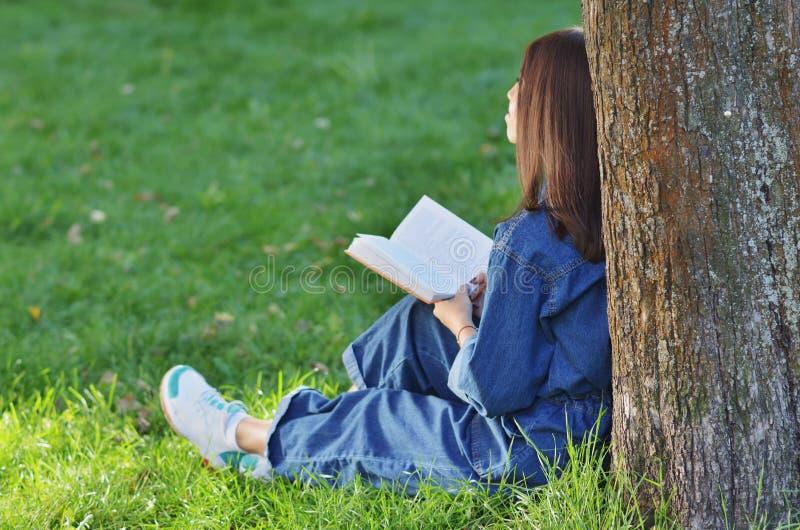 Η νέα όμορφη γυναίκα σπουδαστών κάθεται κοντά στο δέντρο με ένα βιβλίο στα χέρια της και ονειρεύεται με το joyfull και τη χαλαρωμ στοκ εικόνες με δικαίωμα ελεύθερης χρήσης