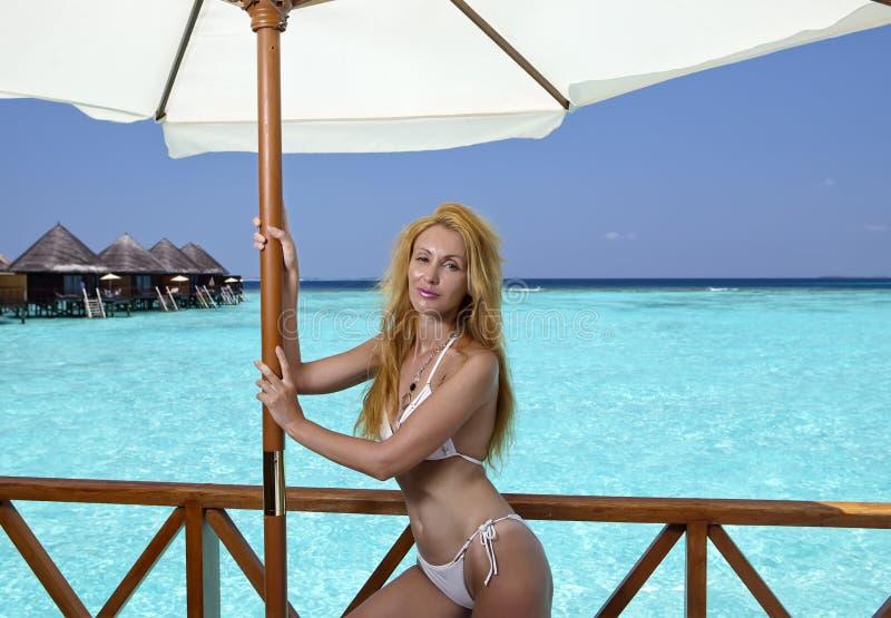 Η νέα όμορφη γυναίκα στέκεται στο κοστούμι λουσίματος στην πλατφόρμα στη βίλα στο νερό, Μαλδίβες στοκ εικόνα με δικαίωμα ελεύθερης χρήσης