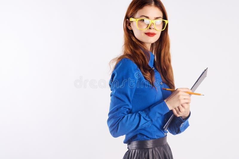 Η νέα όμορφη γυναίκα στα κίτρινα γυαλιά στο άσπρο υπόβαθρο κρατά τα έγγραφα, δάσκαλος, διδάσκει, μελετά στοκ εικόνες
