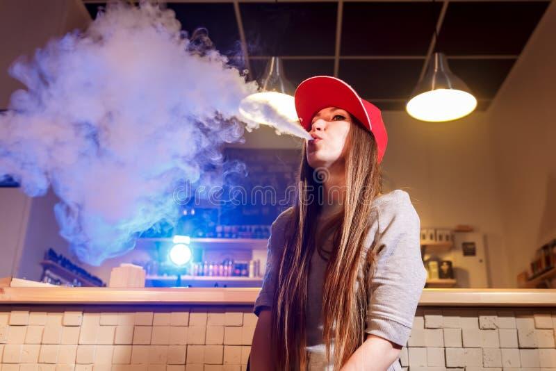 Η νέα όμορφη γυναίκα στην κόκκινη ΚΑΠ καπνίζει ένα ηλεκτρονικό τσιγάρο στο κατάστημα vape στοκ φωτογραφία