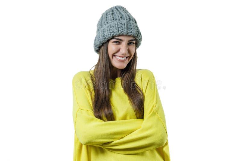 Η νέα όμορφη γυναίκα στο κίτρινο πουλόβερ και τον γκρίζο μεγάλο βρόχο έπλεξε beanie το καπέλο, χέρια που διπλώθηκαν, που εξετάζου στοκ φωτογραφία με δικαίωμα ελεύθερης χρήσης