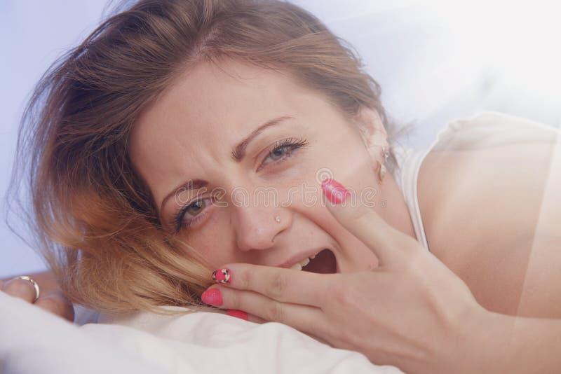 Η νέα όμορφη γυναίκα στο κρεβάτι φορά ` τ θέλει ξυπνήστε στο MO στοκ εικόνες