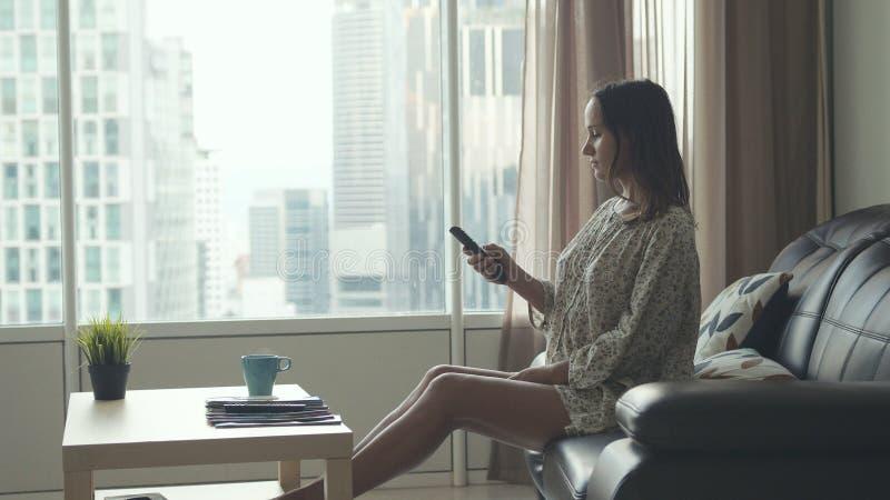 Η νέα όμορφη γυναίκα brunette κάθεται στον καναπέ βάζει τα πόδια της στον πίνακα και χαλαρώνει Το κορίτσι προσέχει τη TV από το π στοκ εικόνες