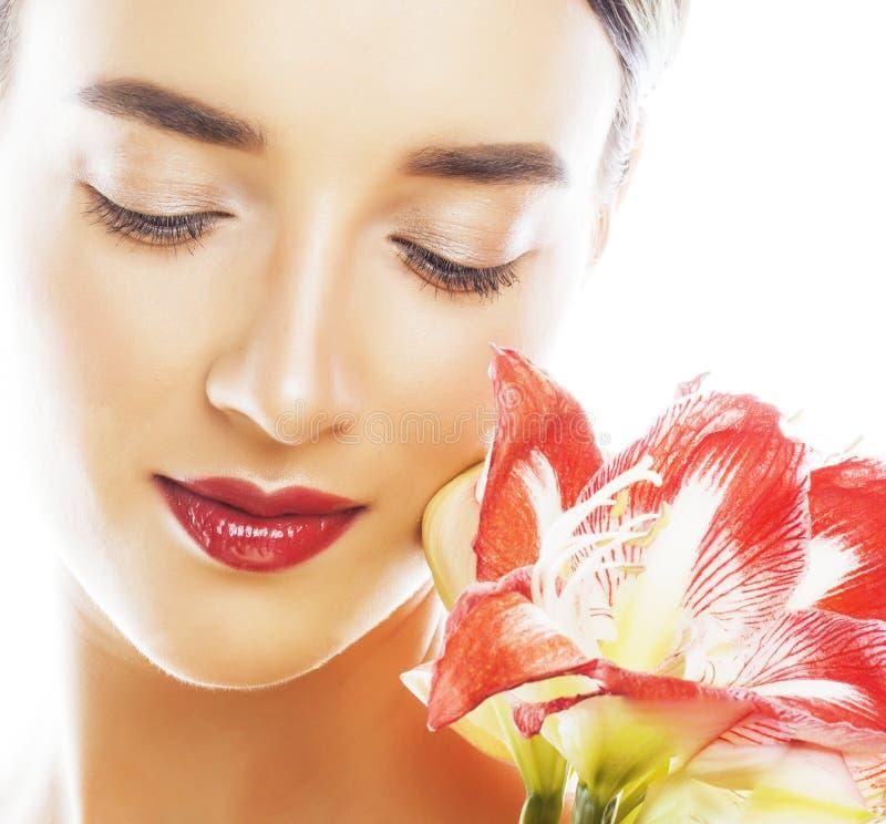 Η νέα όμορφη γυναίκα brunette με τα κόκκινα amaryllis λουλουδιών κλείνει επάνω το ι στοκ εικόνα