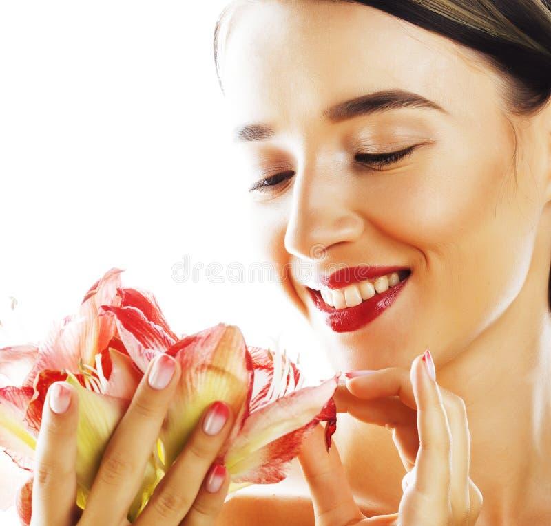 Η νέα όμορφη γυναίκα brunette με τα κόκκινα amaryllis λουλουδιών κλείνει επάνω το ι στοκ φωτογραφία