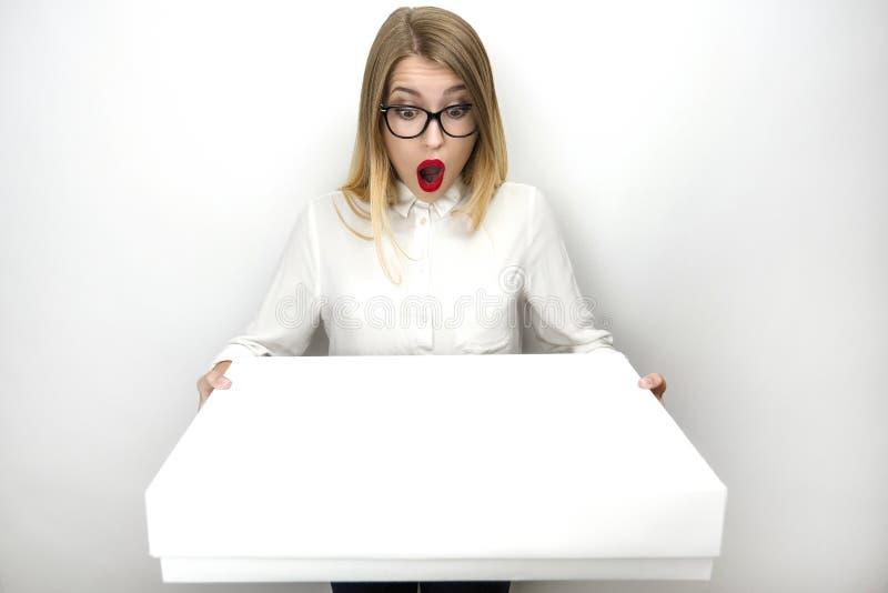 Η νέα όμορφη γυναίκα eyeglasses που φαίνεται πολύ έκπληκτη λαμβάνοντας το δέμα απομόνωσε το άσπρο υπόβαθρο στοκ φωτογραφία με δικαίωμα ελεύθερης χρήσης