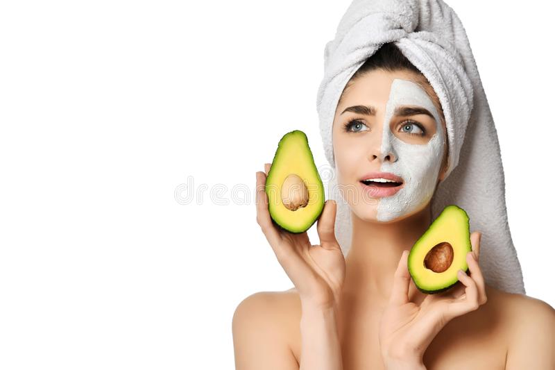 Η νέα όμορφη γυναίκα whalf του προσώπου στην του προσώπου μάσκα και με το άλλο μισό καθαρό κρατά την περικοπή στο μισό φρέσκο αβο στοκ φωτογραφίες