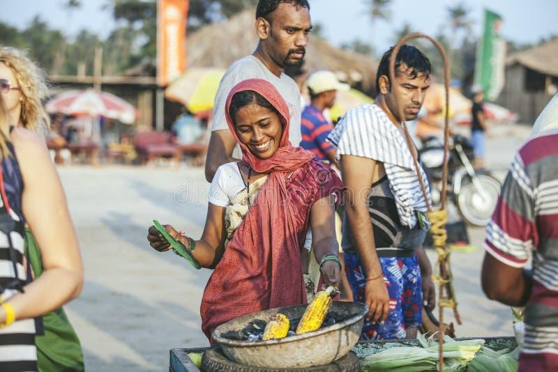 Η νέα όμορφη ινδική γυναίκα γυναικών που καθιστά το καλαμπόκι ψημένο στη σχάρα είναι στοκ εικόνες