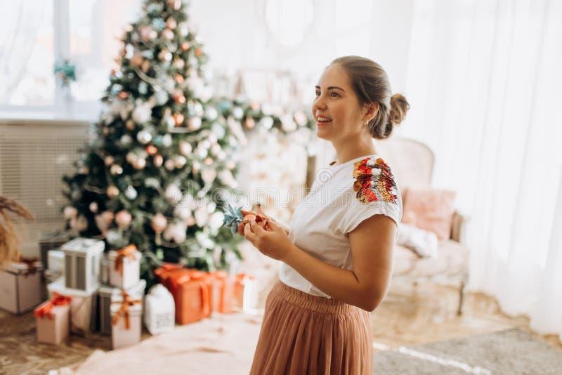 Η νέα όμορφη μητέρα κρατά τις διακοσμήσεις του νέου έτους στεμένος στο στοκ εικόνες