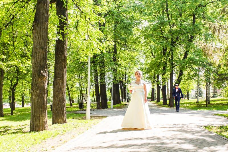 Η νέα όμορφη νύφη περιμένει γιατί ο νεόνυμφος σταθμεύει την άνοιξη στοκ εικόνες