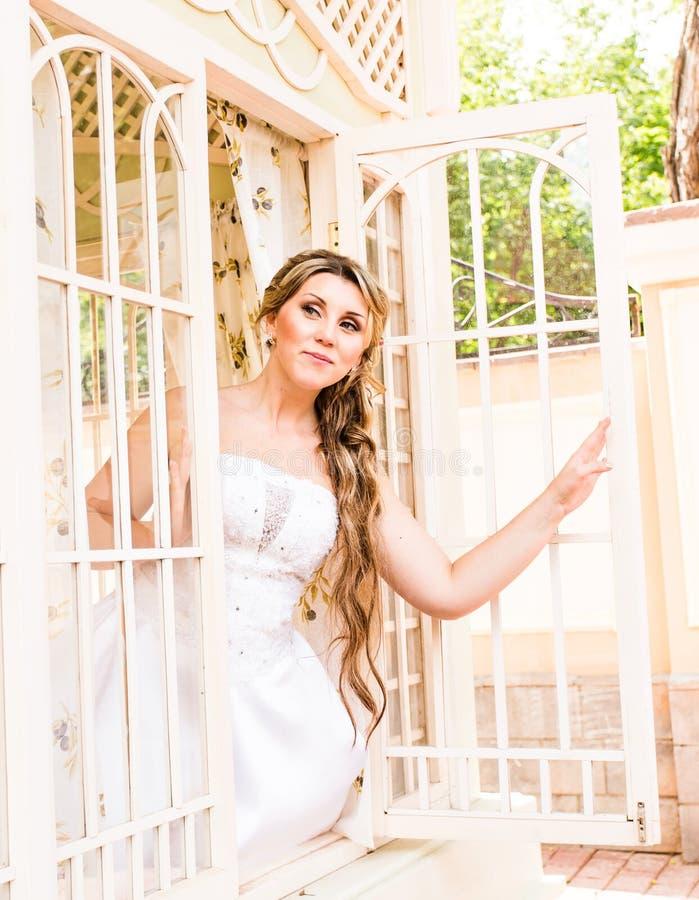 Η νέα όμορφη νύφη περιμένει το νεόνυμφο κοντά στο παράθυρο Όμορφη νύφη αναμμένη από το φως του ήλιου όμορφη νέα αναμονή νυφών στοκ εικόνες με δικαίωμα ελεύθερης χρήσης