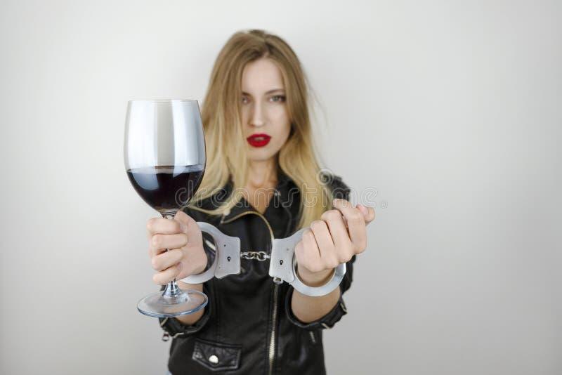 Η νέα όμορφη ξανθή γυναίκα που φορά το μαύρο σακάκι δέρματος πίνει το κρασί και παρουσιάζει δεμένα με χειροπέδες όπλα στο απομονω στοκ εικόνες