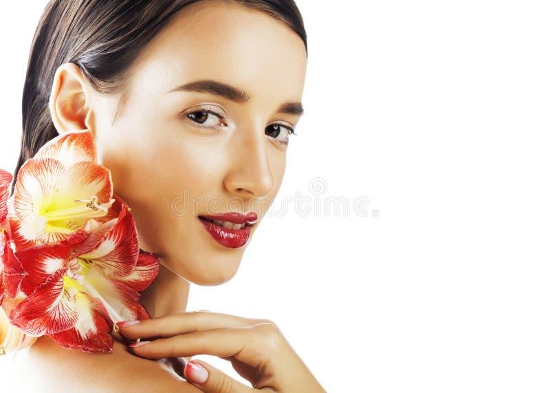 Η νέα όμορφη πραγματική γυναίκα brunette με τα κόκκινα amaryllis λουλουδιών κλείνει στοκ εικόνα