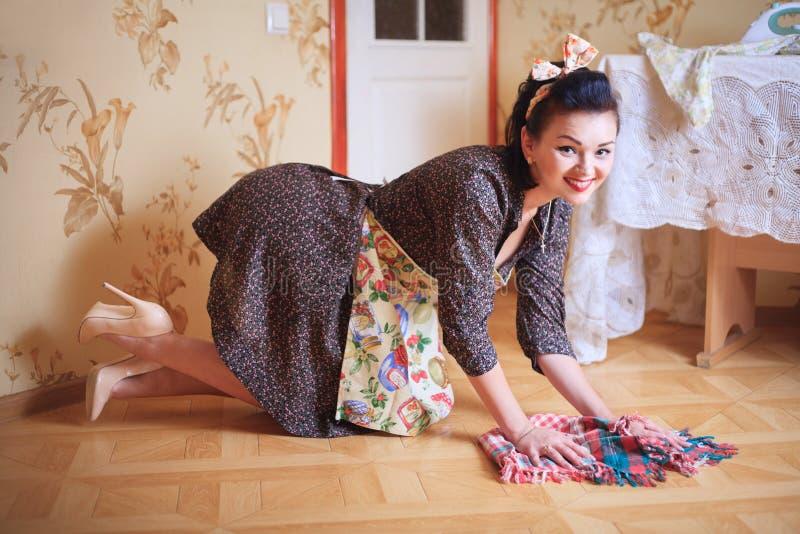Η νέα όμορφη προκλητική γυναίκα πλένει το πάτωμα Πυροβολισμός στο ύφος pinup στοκ εικόνα