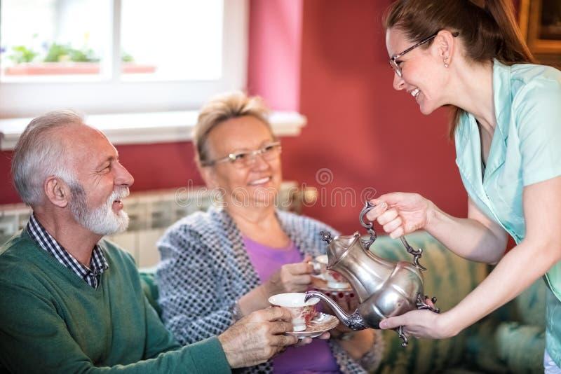 Η νέα όμορφη προσεκτική νοσοκόμα εξυπηρετεί το τσάι για τους ασθενείς στην περιποίηση στοκ εικόνες