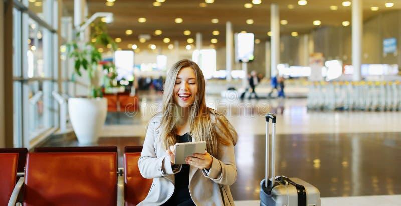 Η νέα όμορφη συνεδρίαση γυναικών στην αίθουσα αερολιμένων με την ταμπλέτα και, χρησιμοποιώντας Διαδίκτυο στοκ εικόνες