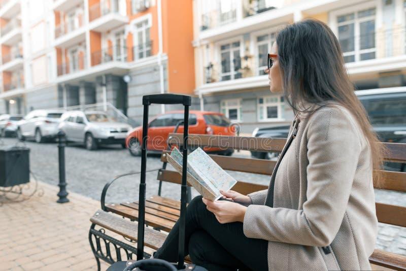 Η νέα όμορφη συνεδρίαση γυναικών στον πάγκο με τη βαλίτσα ταξιδιού και το χάρτη πόλεων ανάγνωσης, πίνει τον καφέ, υπόβαθρο οδών π στοκ εικόνες