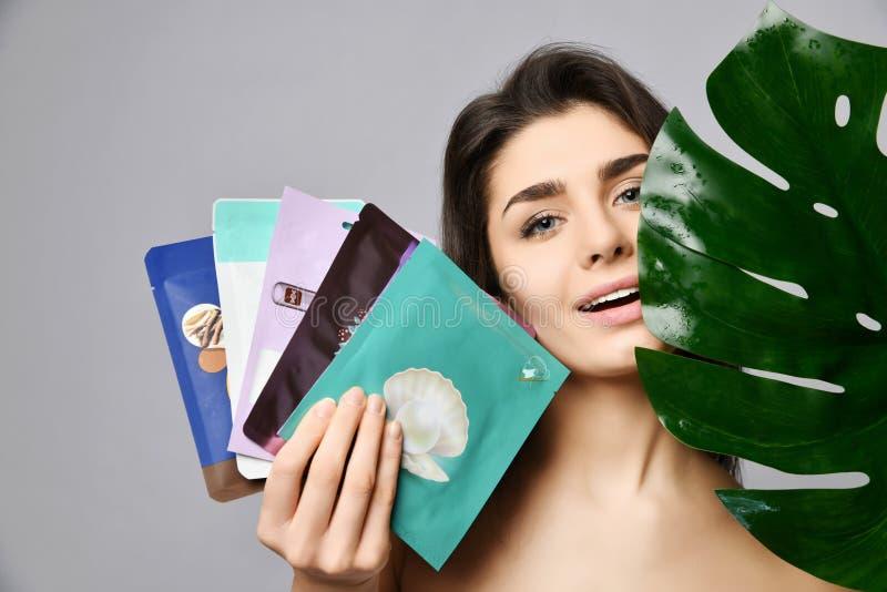 Η νέα όμορφη antcipating ευχαρίστηση γυναικών της φροντίδας κρατά ένα σύνολο συσκευασμένων καλλυντικών μασκών και ενός μεγάλου πρ στοκ φωτογραφίες