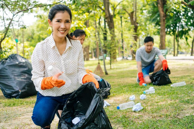 Η νέες ασιατικές γυναίκα και η ομάδα εθελοντών φορούν τα γάντια και συλλέγουν τα απορρίματα στην τσάντα δοχείων απορριμμάτων στο  στοκ εικόνες με δικαίωμα ελεύθερης χρήσης