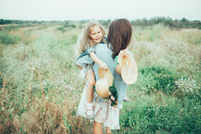 Η νέες μητέρα και η κόρη στην πράσινη χλόη στοκ εικόνες