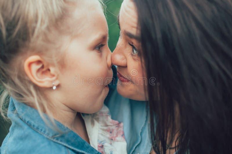 Η νέες μητέρα και η κόρη στην πράσινη χλόη στοκ φωτογραφίες